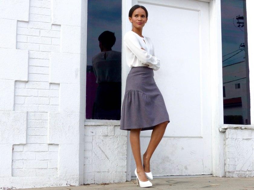 Amanda Garrigus in lavender skirt and white pumps