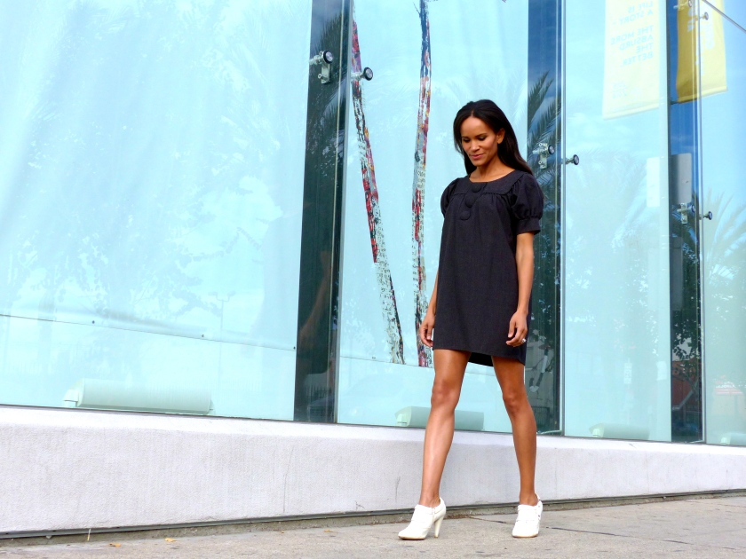 Amanda Garrigus wearing a white bootie and grey flannel dress outside Michael Kohn Gallery