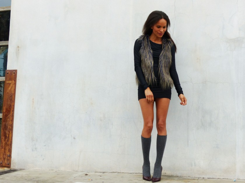 Amanda Garrigus Faux Fur Vest and grey socks against a grey wall 1
