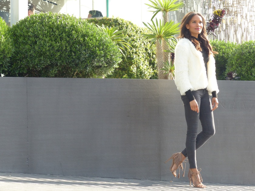 Amanda Garrigus in fringe sandals and a fuzzy white puffy jacket