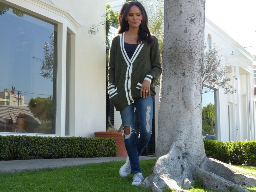 Amanda Luttrell Garrigus in an olive striped sweater and ripped jeans