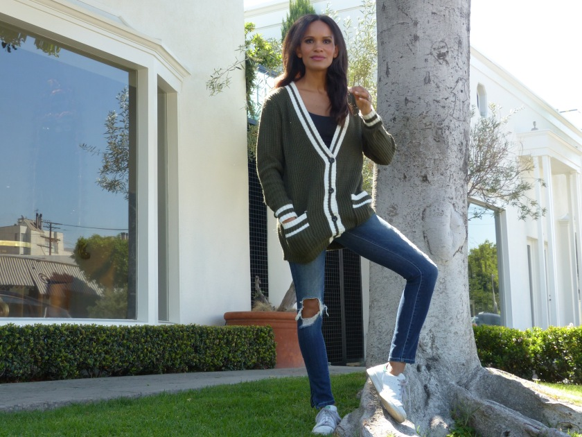 Amanda Luttrell Garrigus in an olive striped sweater, ripped jeans and stan smiths