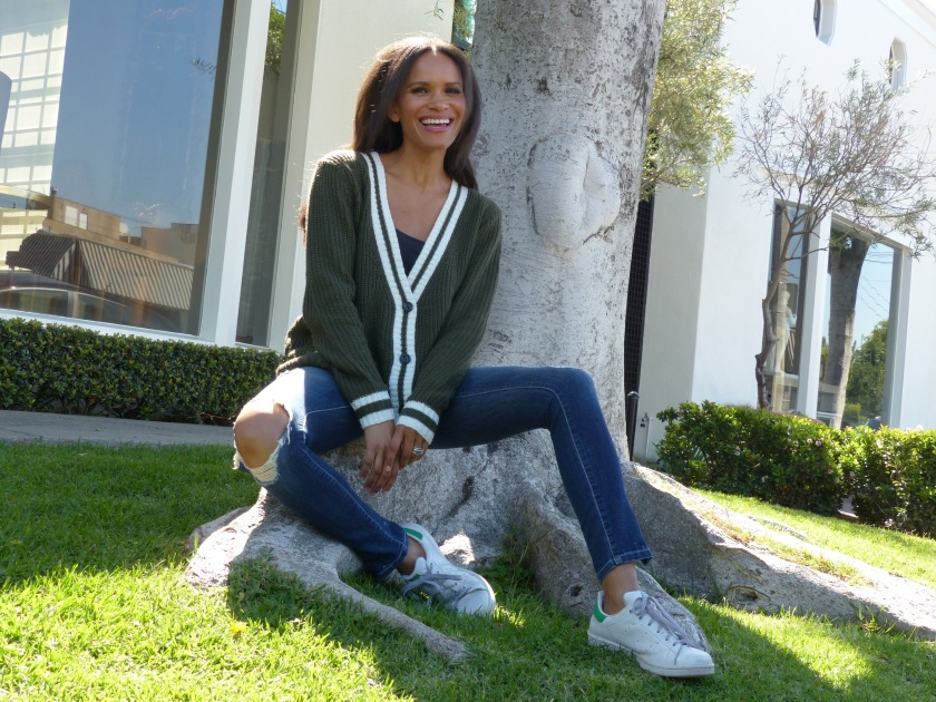 Amanda Luttrell Garrigus smiling in a striped sweater and ripped jeans