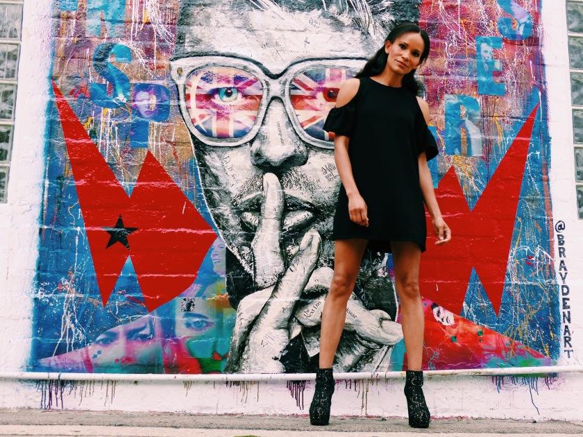 Amanda Luttrell Garrigus wearing an open shoulder dress in front of a David Bowie mural