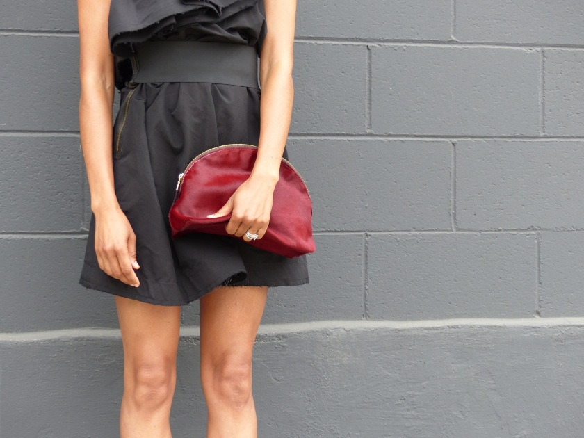 Amanda Luttrell Garrigus wearing black one shoulder Lanvin for H&M dress and carrying Cindy Daly oxblood pony clutch
