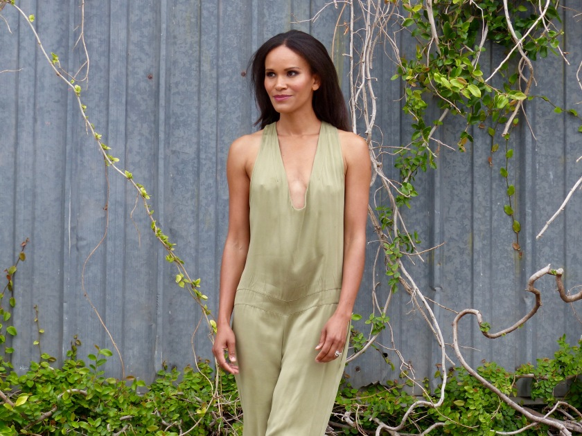 Amanda Luttrell Garrigus wearing an olive silk jumpsuit with plunging neckline