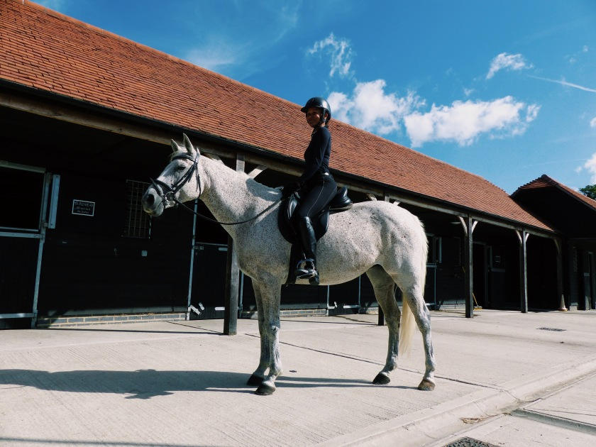 Amanda Garrigus riding a grey mare at the four seasons hampshire