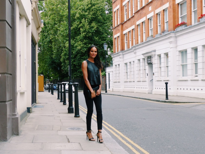 Amanda Luttrell Garrigus in London wearing Zara black vegan leather top and YSL clutch