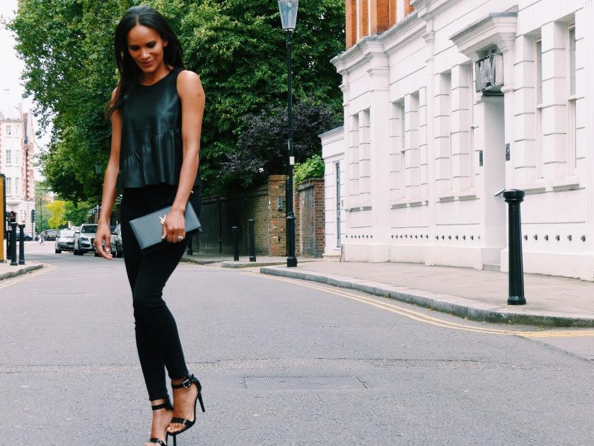 Amanda Garrigus in black jeans and black vegan leather top with black YSL clutch