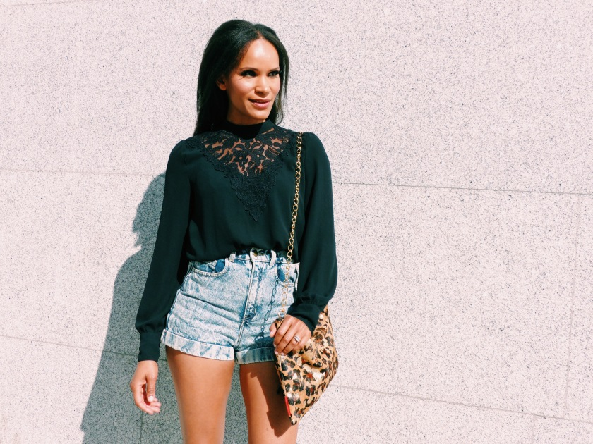 Amanda Garrigus in high-waisted shorts and a black long sleeve top, carrying a leopard bag