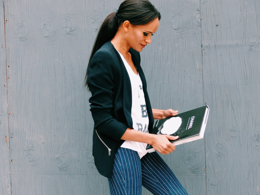 Amanda Garrigus wearing a black jacket and striped pant with a Chanel book