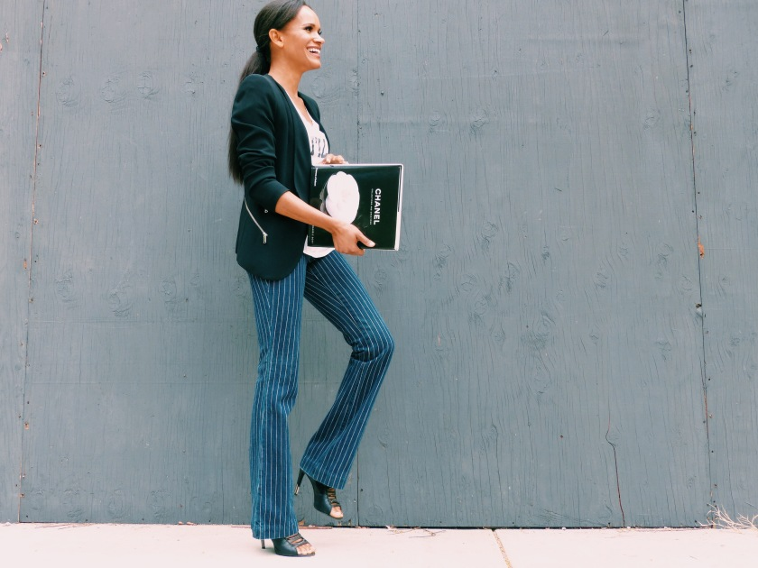 Amanda Luttrell Garrigus wearing a black jacket and striped pant with a Chanel book