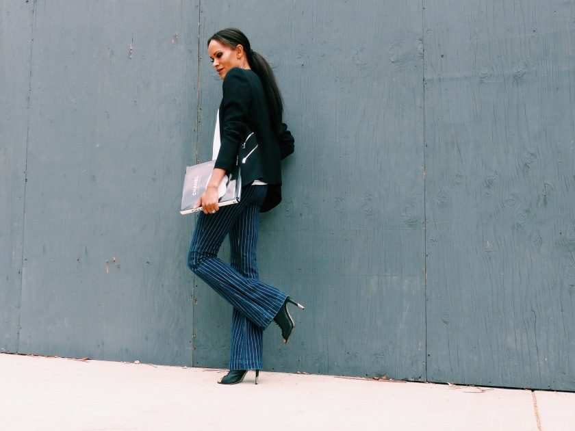 Amanda Garrigus wearing a black jacket and striped pant carrying a Chanel book