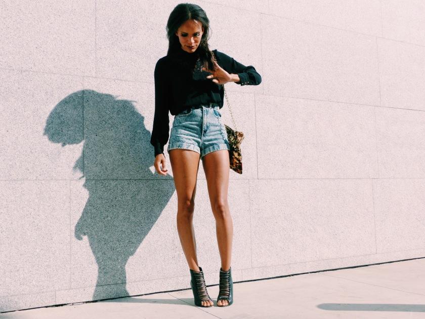 Amanda Luttrell Garrigus wearing denim shorts and a black long sleeve top, carrying a leopard bag