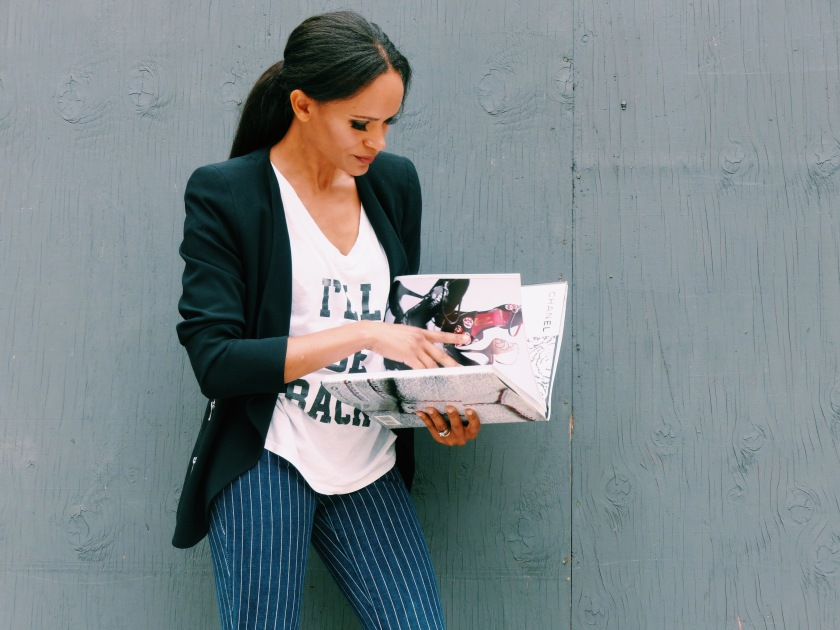 Amanda Luttrell Garrigus in a graphic T and reading a Chanel book
