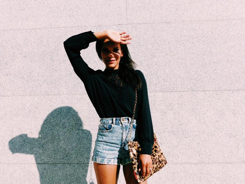 Amanda Garrigus in denim shorts and a black long sleeve top, carrying a leopard bag