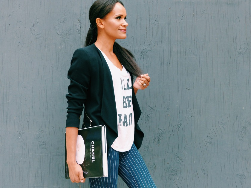 Amanda Luttrell Garrigus wearing a black jacket, striped pant and graphic T-shirt, carrying a Chanel book