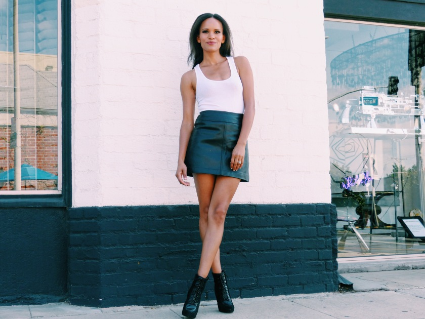 Amanda Luttrell Garrigus in a white scoop neck tank and a black leather mini