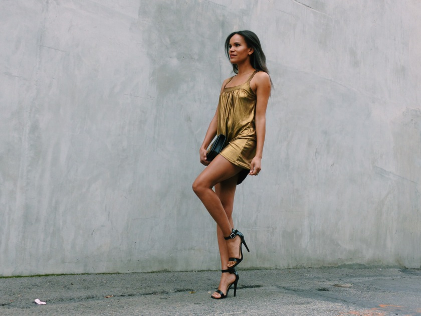 Amanda Garrigus wearing a liquid gold metallic dress and carrying a YSL Clutch