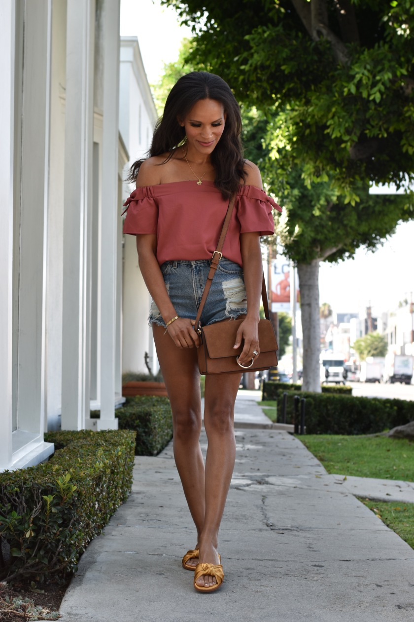 Amanda Garrigus in a rust colored off the shoulder top and distressed denim