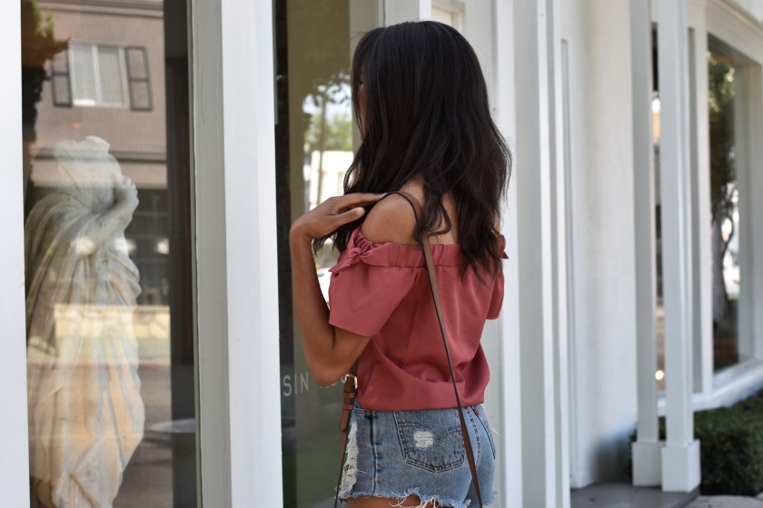 Amanda Luttrell Garrigus window shopping in an off the shoulder top and denim cut offs